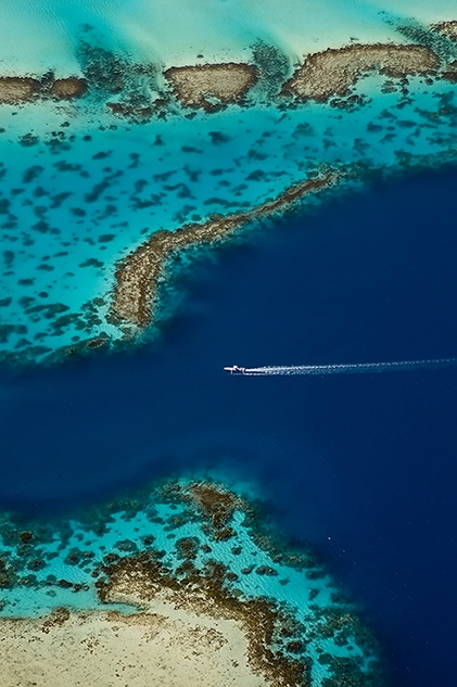 Aerial view a speedboat making its way through the lagoon of Bora Bora in French Polynesia .