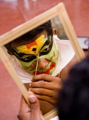 Kathakali artist making up.